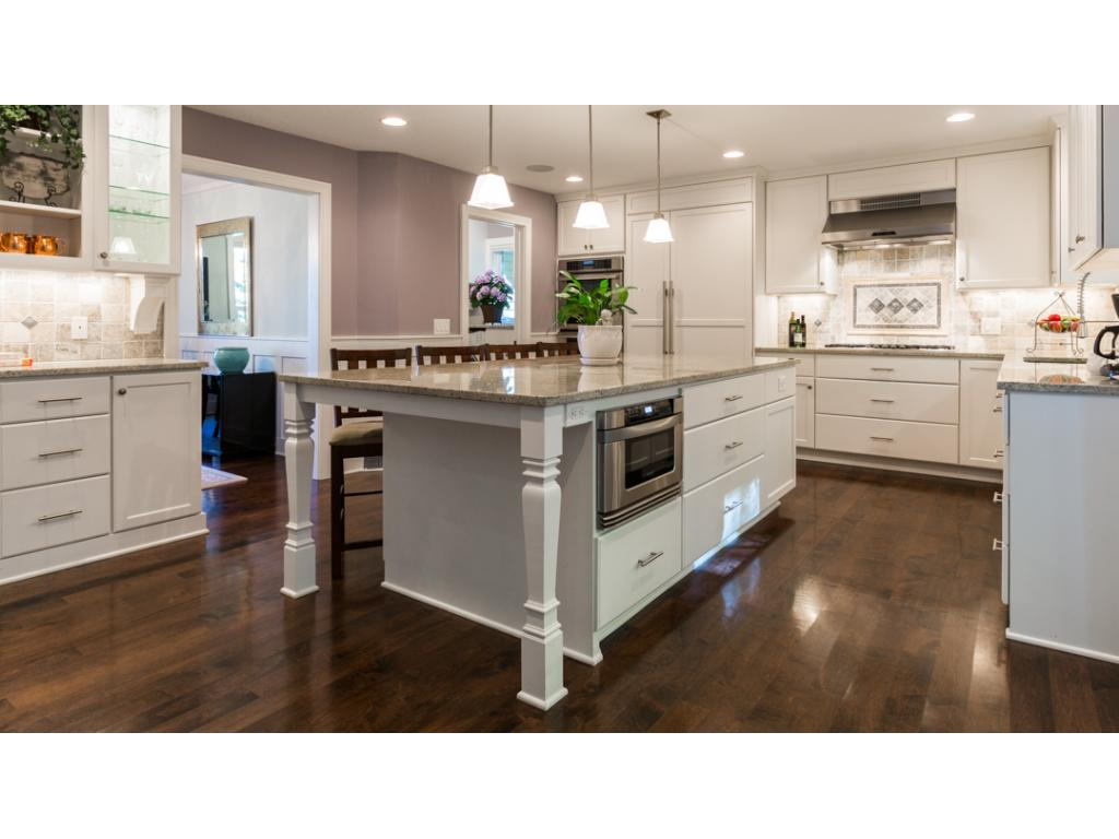 "The stone backsplash accents the custom painted cabinets featuring soft-close drawers & doors. Recessed lighting & stylish pendant lights over the island make the granite sparkle! Gorgeous 3/4"" solid maple hardwood floors sweep thru the main level."