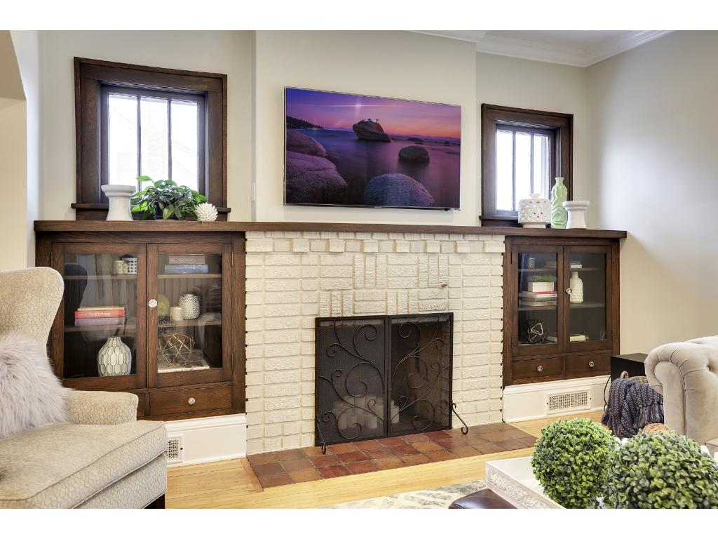 This gorgeous fireplace centers the living room and is flanked with gorgeous built ins topped with piano windows allowing for plenty of natural light.