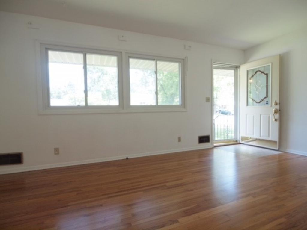 Another view of the living room showing the large, updated picture windows and attractive front door