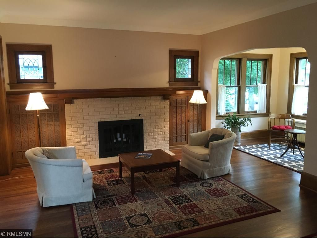 Wood burning Fireplace surrounded by bookcases and framed by leaded glass windows.