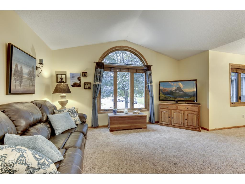 Large living room with huge front window, vaulted ceilings, and new carpet!