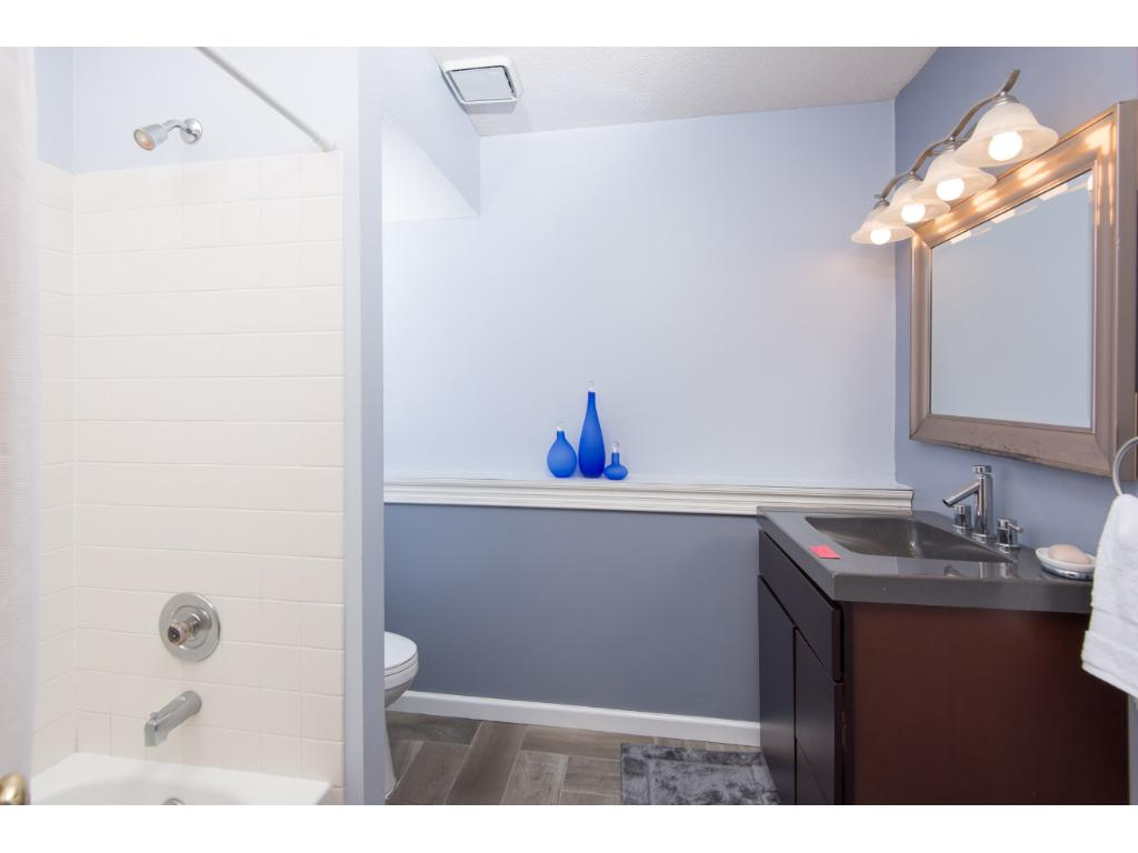 Lower level bathroom with granite counter top and tiled floors.