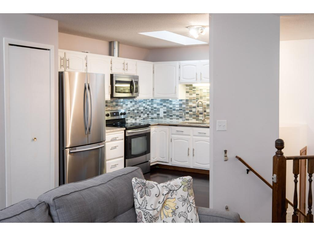 Granite counter top and stainless steel appliances. Glass backsplash
