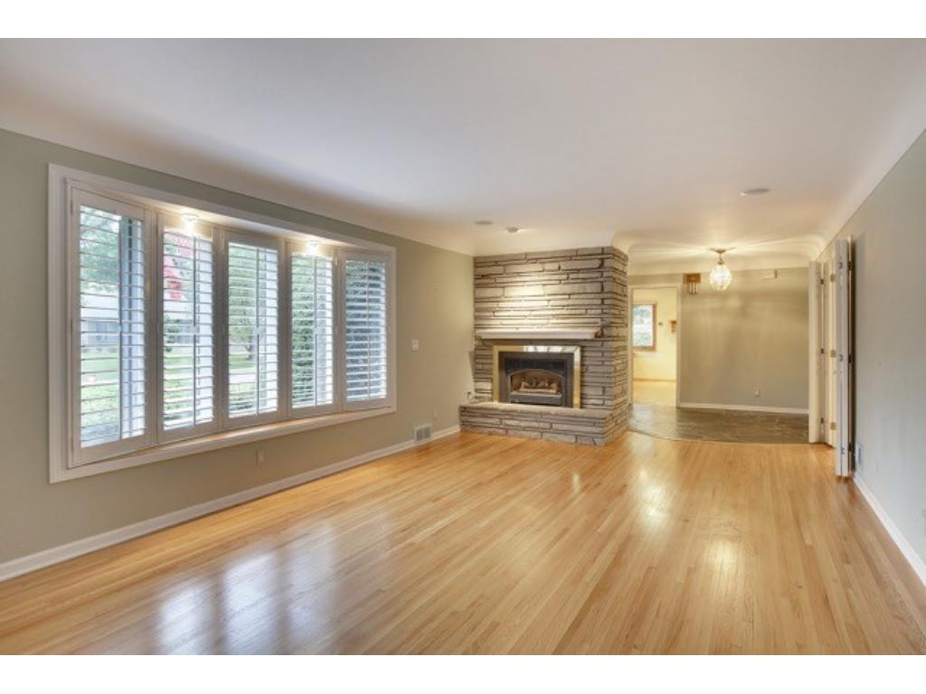Living Room with gleaming hardwood floors, plantation shutters and fireplace with gas insert.