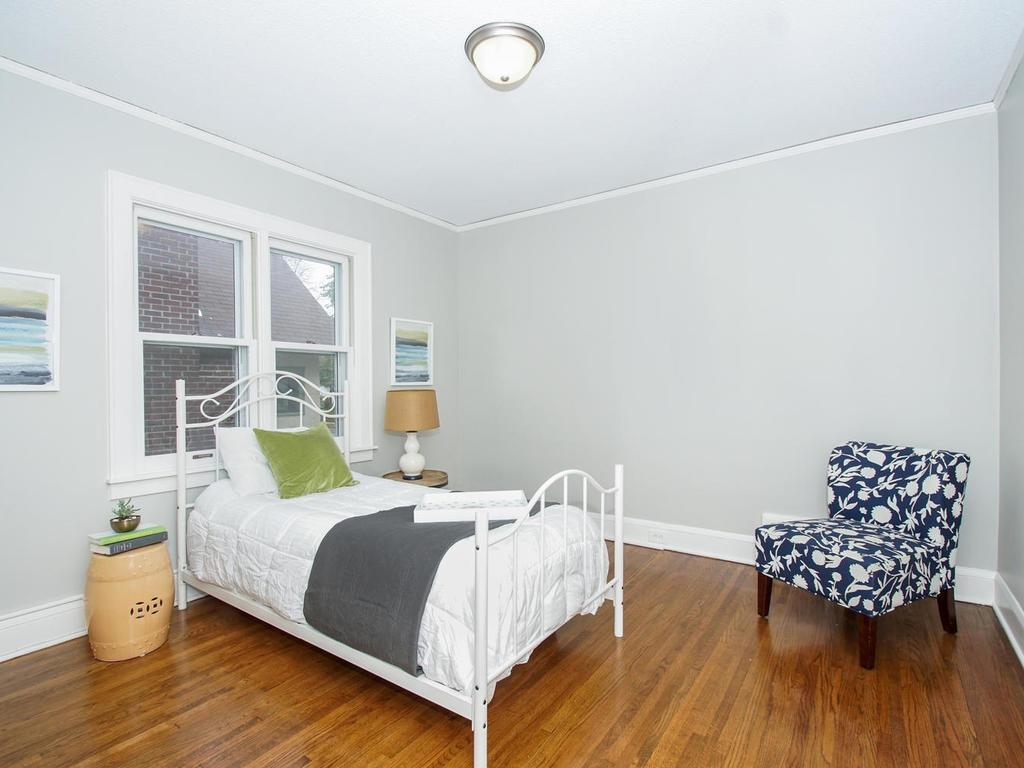 Cheery 2nd main floor bedroom has refinished hardwood floors and is decorated in neutral tones.