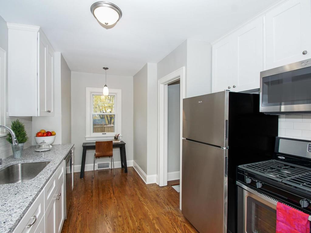 Kitchen has hardwood floors, new cabinets, granite counters, stainless farm sink, stainless appliances & more.