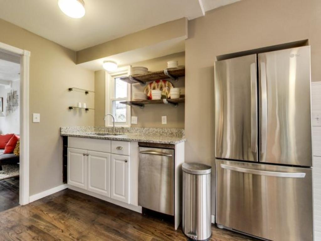 This quaint kitchen features a mix of modern and rustic look, and includes stainless steel appliances.