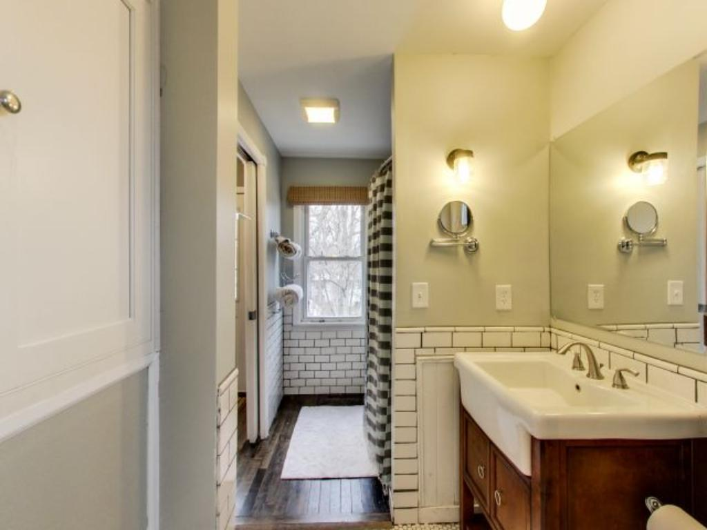 Accessible via the back entry and bedroom, this bathroom features a farm-house style sink and tiled walls to give it more character.
