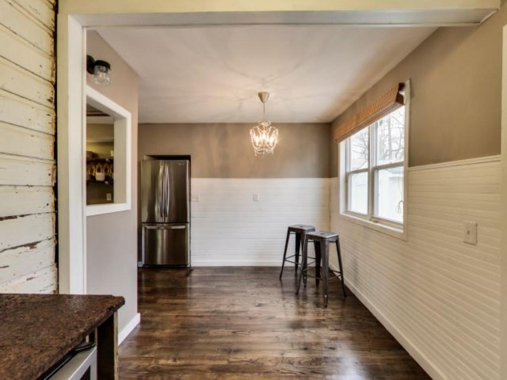 This cozy dining room features a nice rustic look with walls styled with wooden boards.