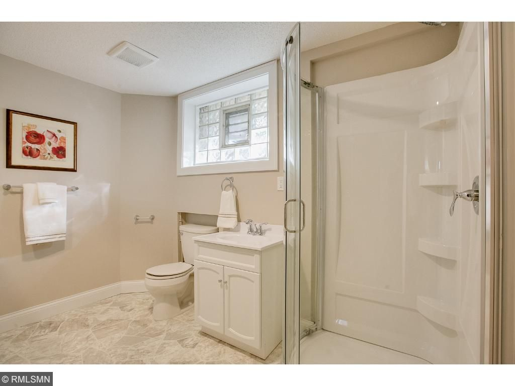 lower level 3/4 bath has great storage space and a very cool circular shower to keep the original Frank Lloyd Wright character of the home!