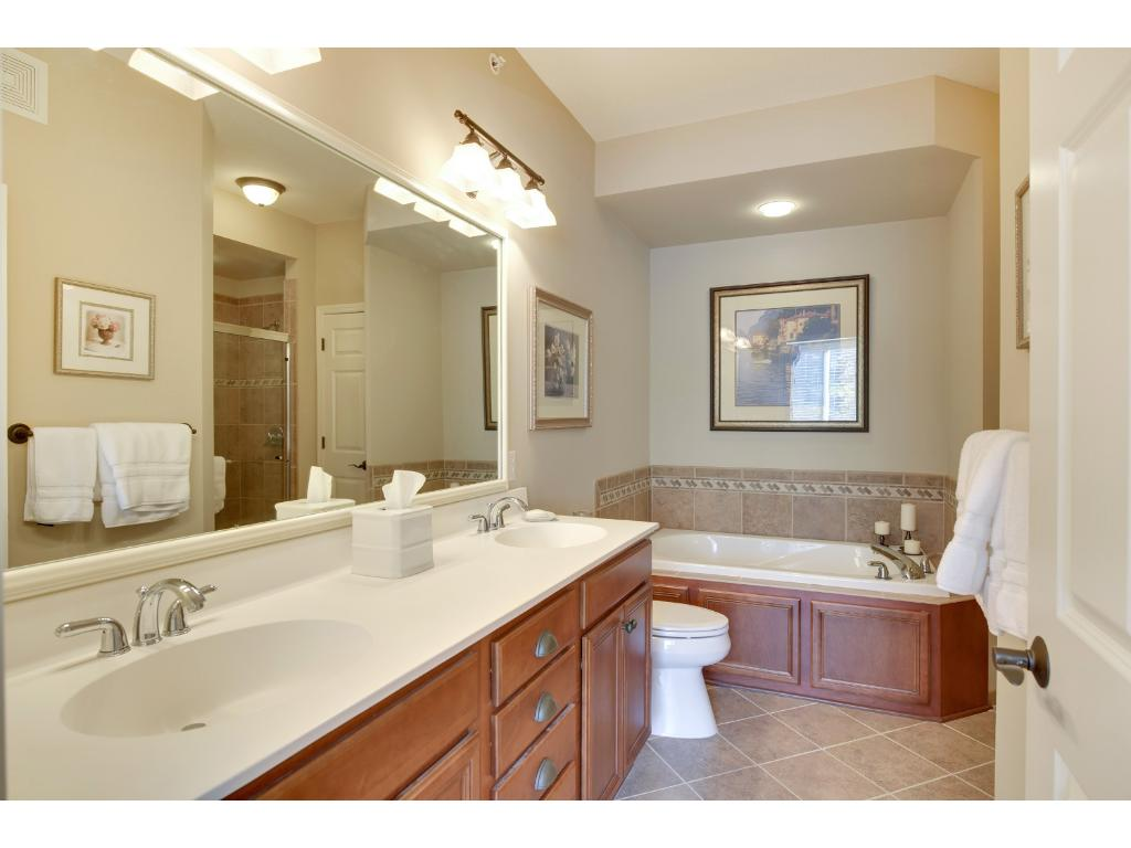 The ceramic tiled master bathroom features a dual vanity, a large soaking tub and a separate tiled step-in shower