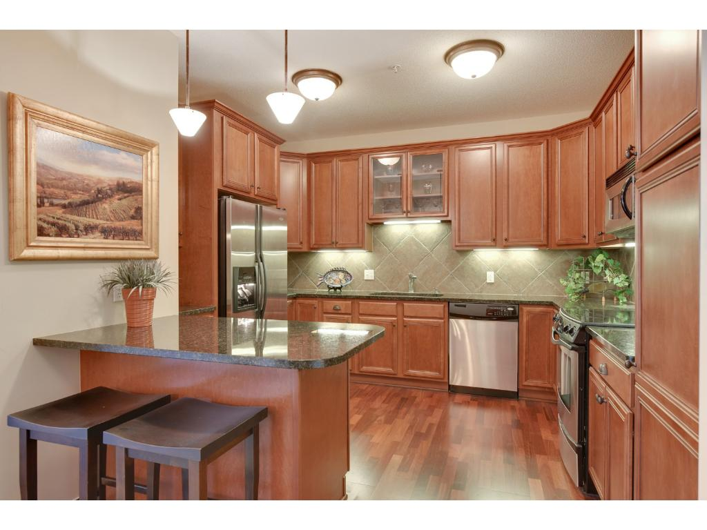 The cherry kitchen features an abundance of counter space including a convenient breakfast bar peninsula