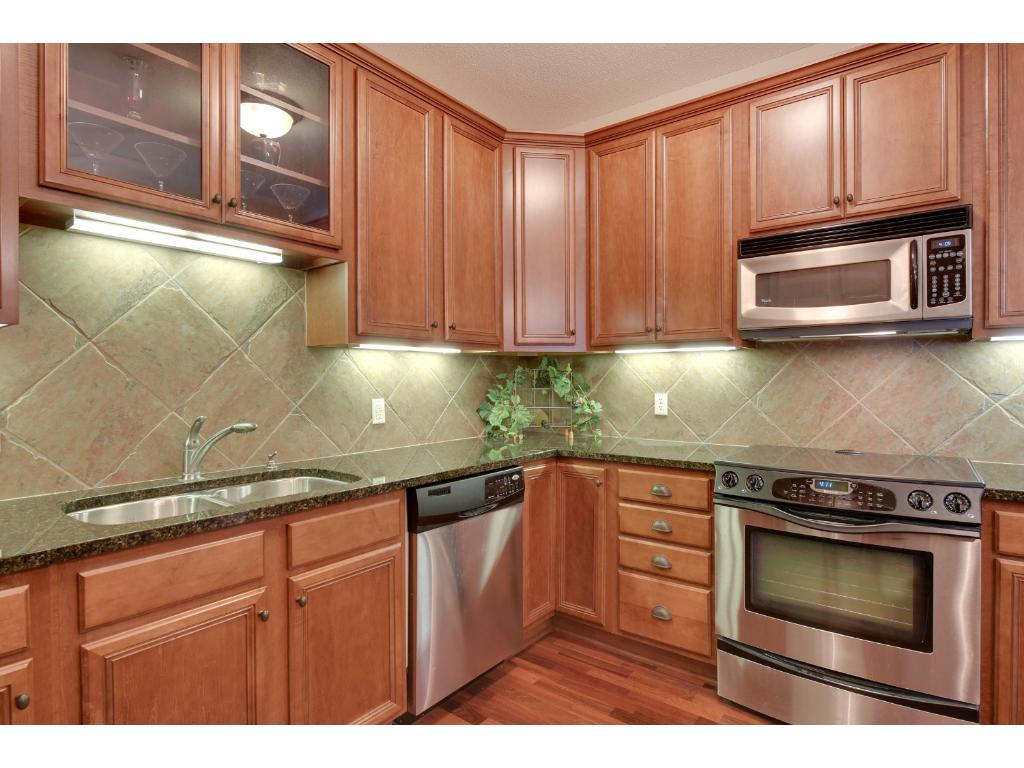 The kitchen is accentuated with stainless steel appliances, under cabinet lighting and a tile backsplash