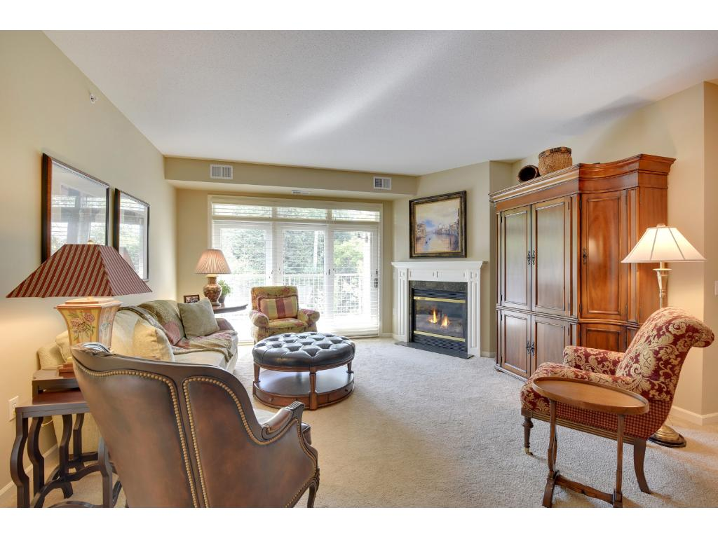The living room has a wall of west facing windows with transoms and is accentuated by a gas fireplace
