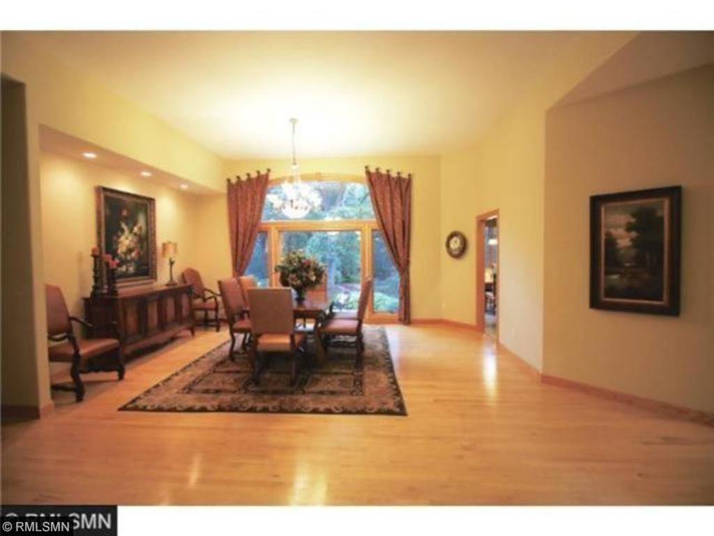 Formal Dining Room features gleaming hardwood floors. Overlooks lovely landscaping & water feature.