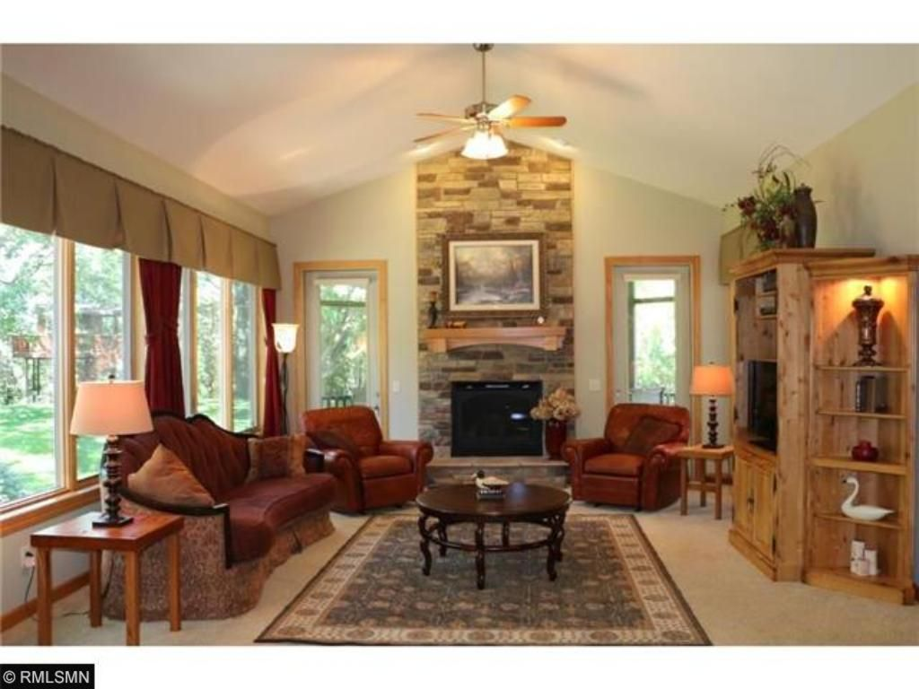Main level Great Room boasts floor to ceiling fireplace. Screen Porch beyond. Enjoy abundant wildlife just outside