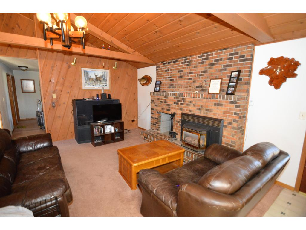 Brick fireplace with vaulted ceiling in the living room.