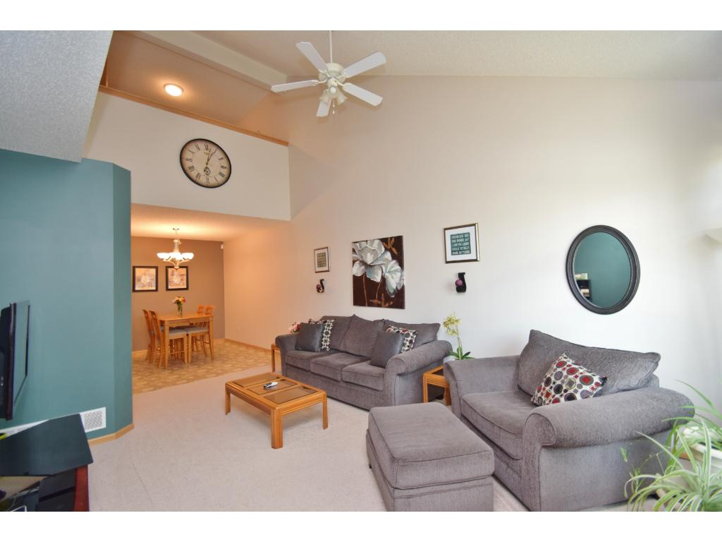 View of living room upon entry of home. Brand new carpet. Vaulted ceilings, ceiling fan, loft on upper level overlooks this space. Stairs are to the left lead to upper level.