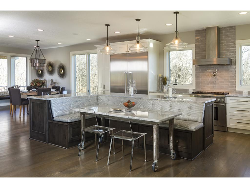 Stainless appliances with a breakfast nook built in to the giant center island.