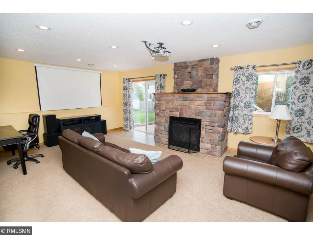 Warm & welcoming family room features a stone gas fireplace, projector with movie screen, and patio door out to the backyard.