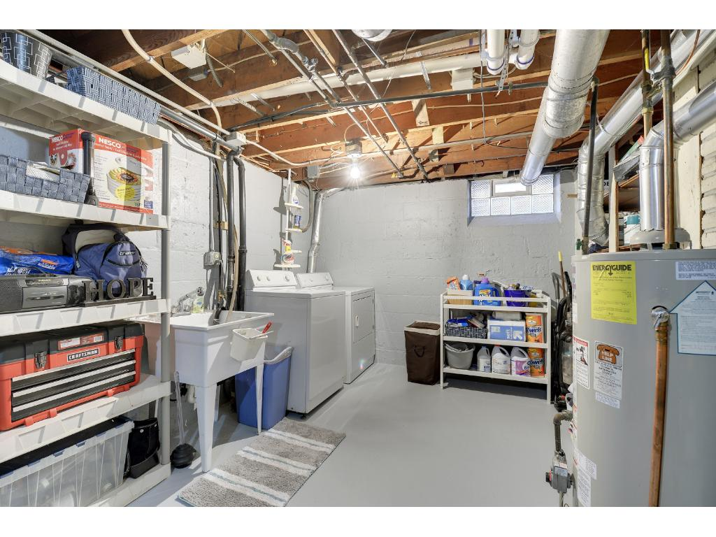 Laundry room is clean and bright with extra storage space.