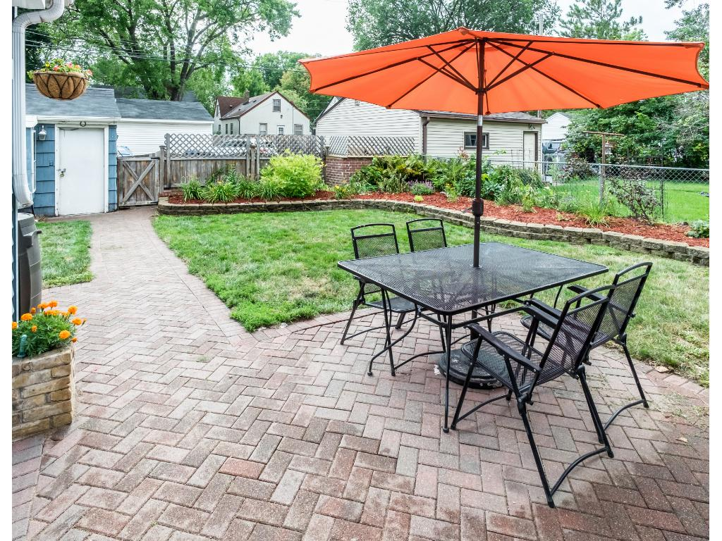Spacious fenced in back yard with paver stone patio and gardens.