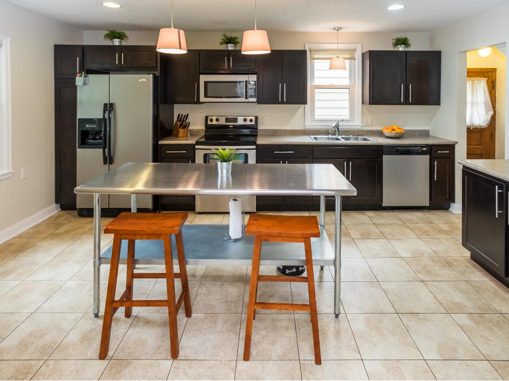 Remodeled kitchen with tiled floors and stainless steel front appliances.