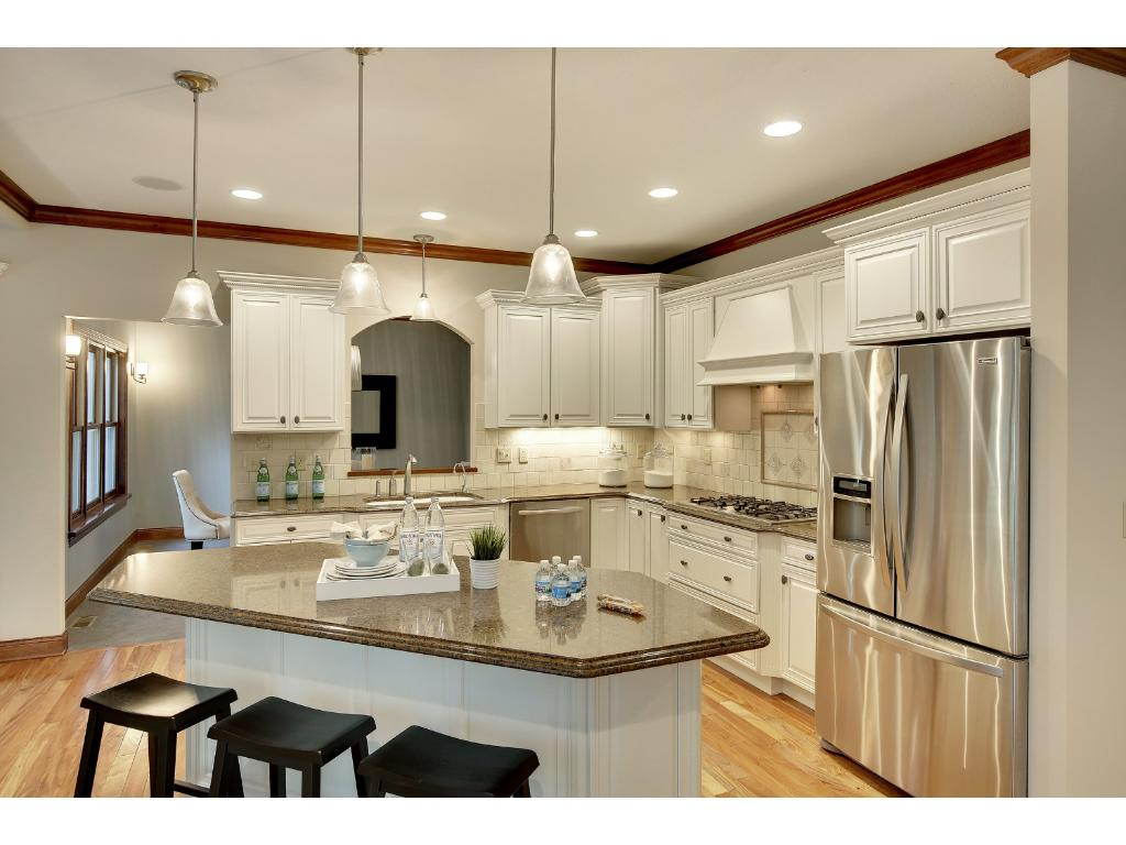 The open, white Kitchen sits at the heart of the house and is open to the Family Room, Informal Dining and Deck with a pass-through to the Formal Dining and Living Room.