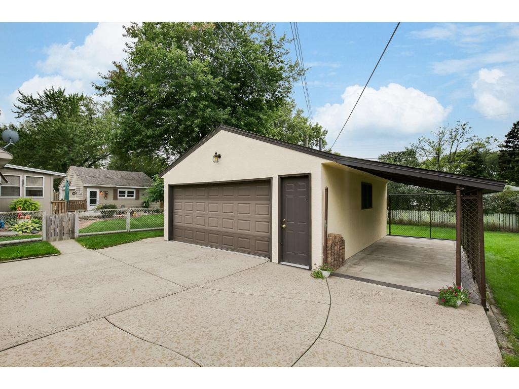 Over sized two car garage with a great concrete driveway and covered area to protect your toys.