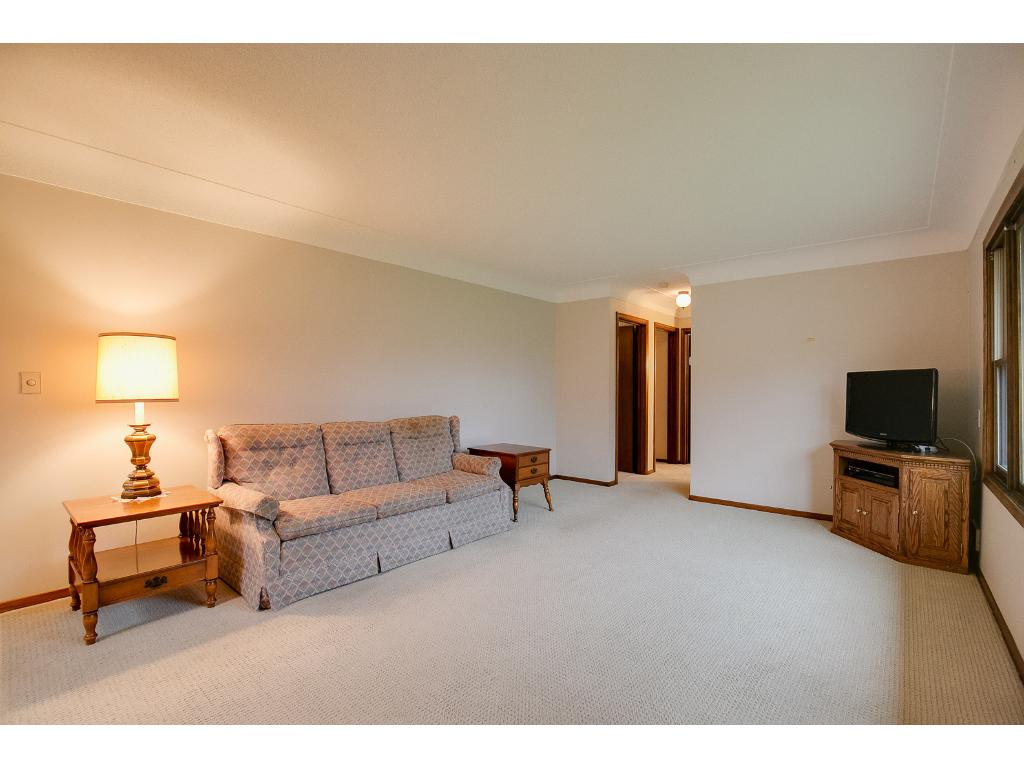 The spacious living room features a beautiful front window. Underneath the carpet lies the original hardwood floors!