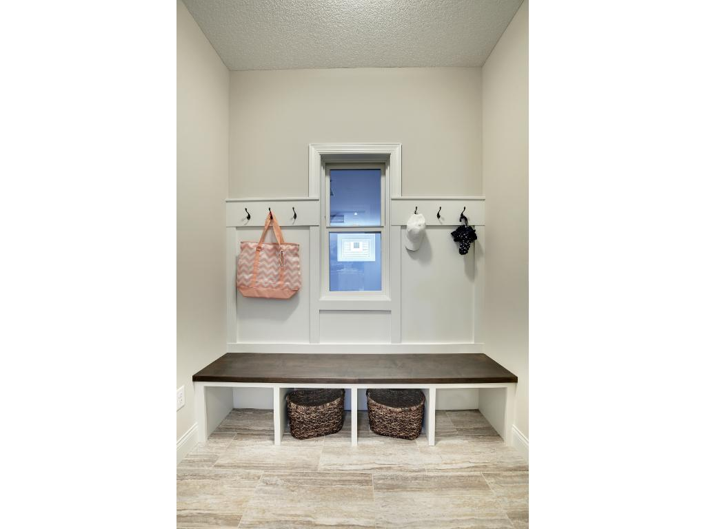 The mudroom area provides bench seating, storage and hooks.