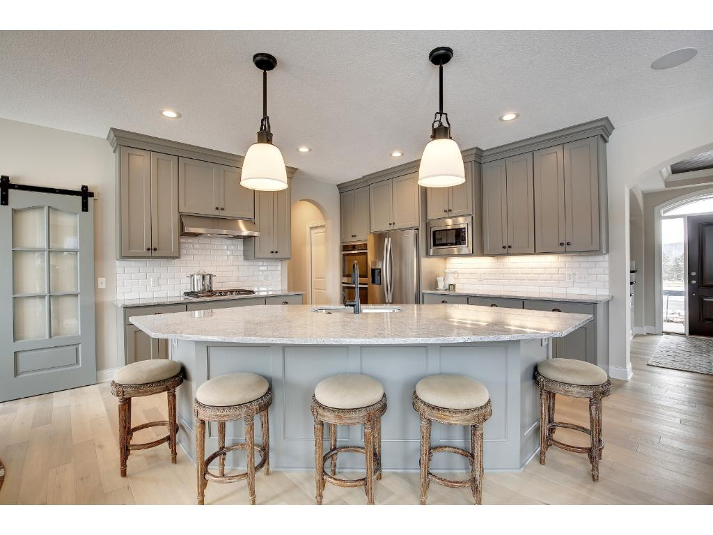Large granite kitchen island with seating and storage adds to the functionality of this beautiful kitchen.
