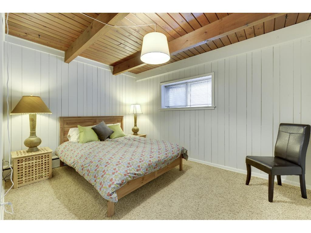 Lower level Bedroom #4 (non-conforming) with exposed beam ceiling.