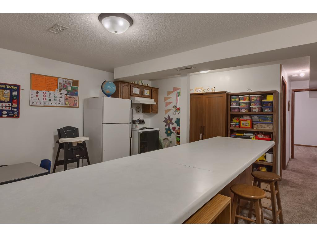 This lower level kitchen features a stove, full size refrigerator and extra seating at the counter-top.