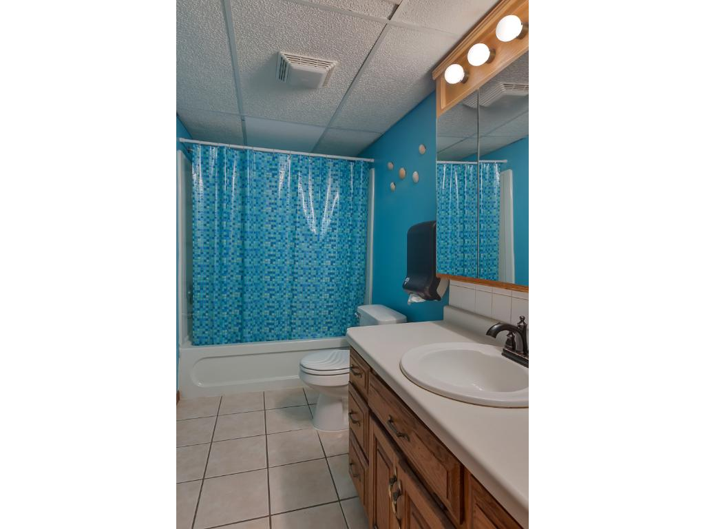 The lower level bathroom also has a large vanity with a good amount of storage space in the cabinets and drawers.