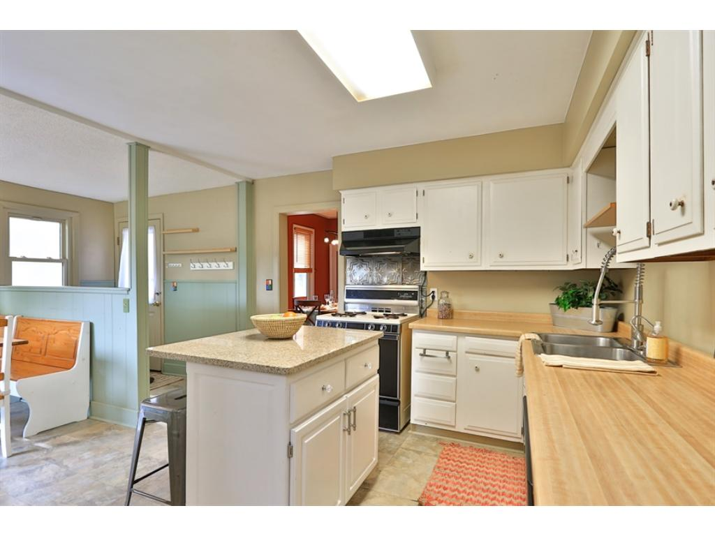This is a large kitchen, including both a working island and an eat-in dining area.