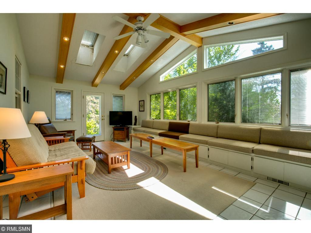 Sun room has skylights and vaulted ceilings as well as bench sitting along the width of windows.