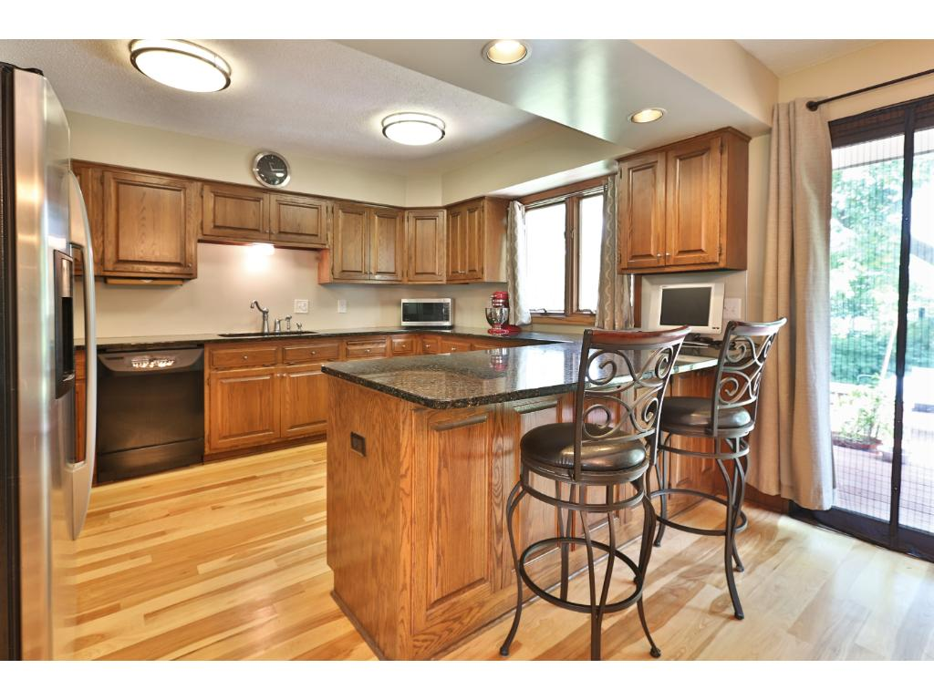Lovely breakfast bar area in kitchen with granite, stainless appliances, wood burning fireplace to relax in front of on cold winter mornings, excellent space and storage.