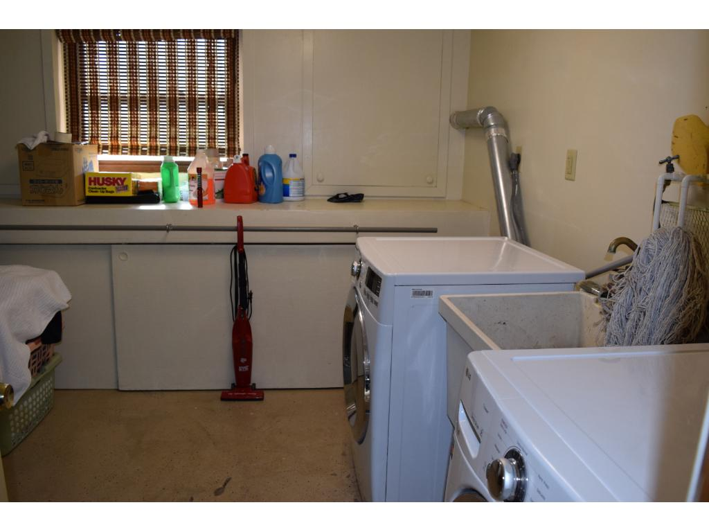 Large laundry room with cabinets, a folding surface and its own double closet