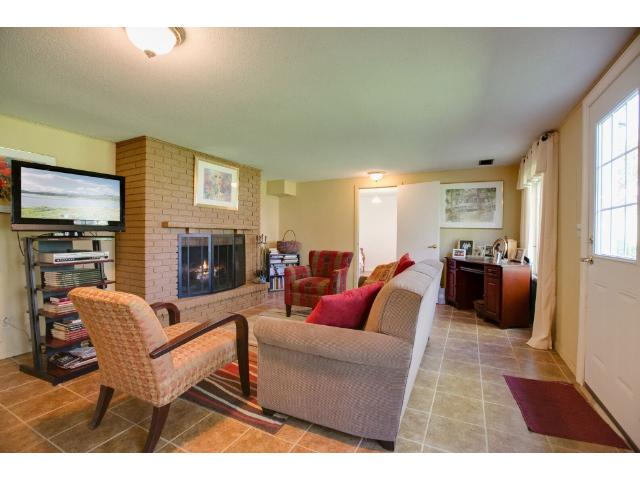 Opposite view lower level family room with fireplace and tiled floors.