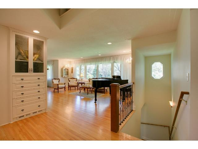 Foyer to living room and lower level stair view.  Wall of back windows over looking very private 1/3 acre lot, trees & privacy galore!