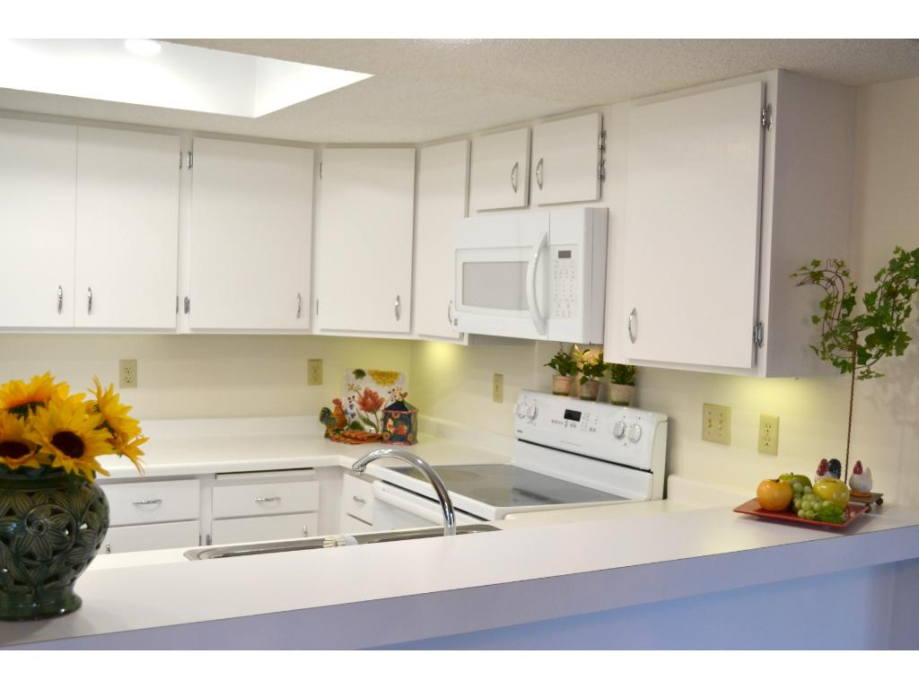The bright, updated kitchen features new white countertops and flooring.