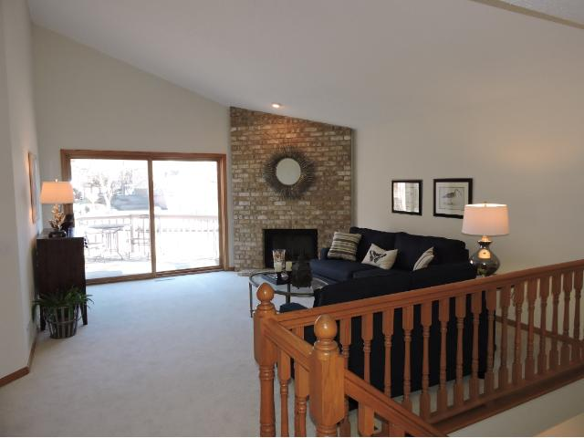 Vaulted ceiling in living room with deck and wood burning fireplace.
