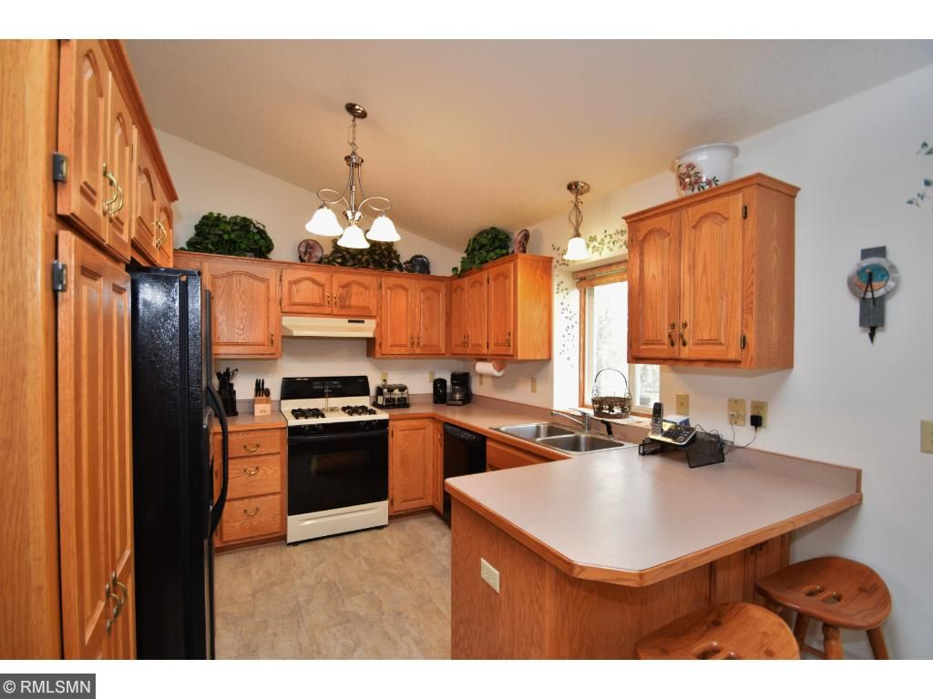 Kitchen has raised custom cabinets & breakfast bar
