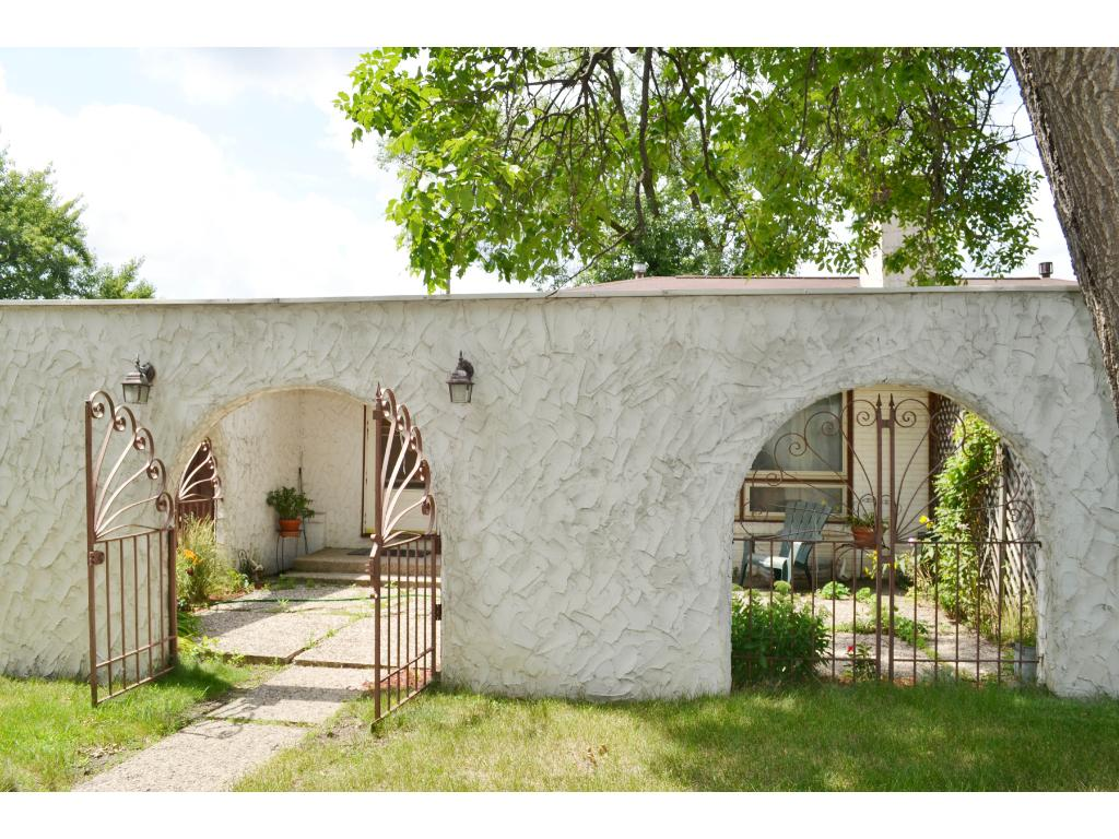 Set back from Xerxes Avenue with arched gates that open to large front patio
