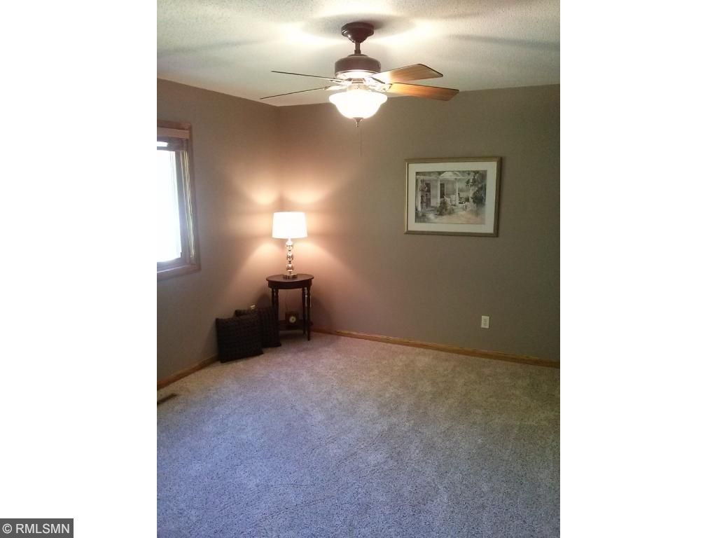 Owners bedroom includes updated fixture and ceiling fan.