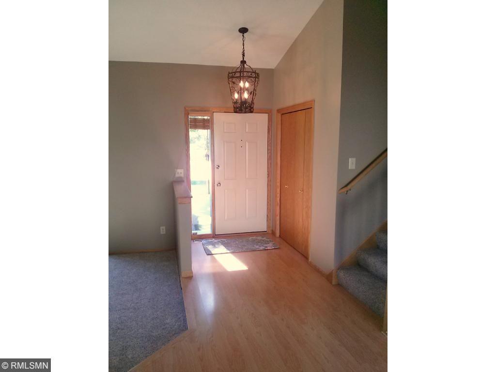 Gracious foyer with large coat closet and designer light fixture.
