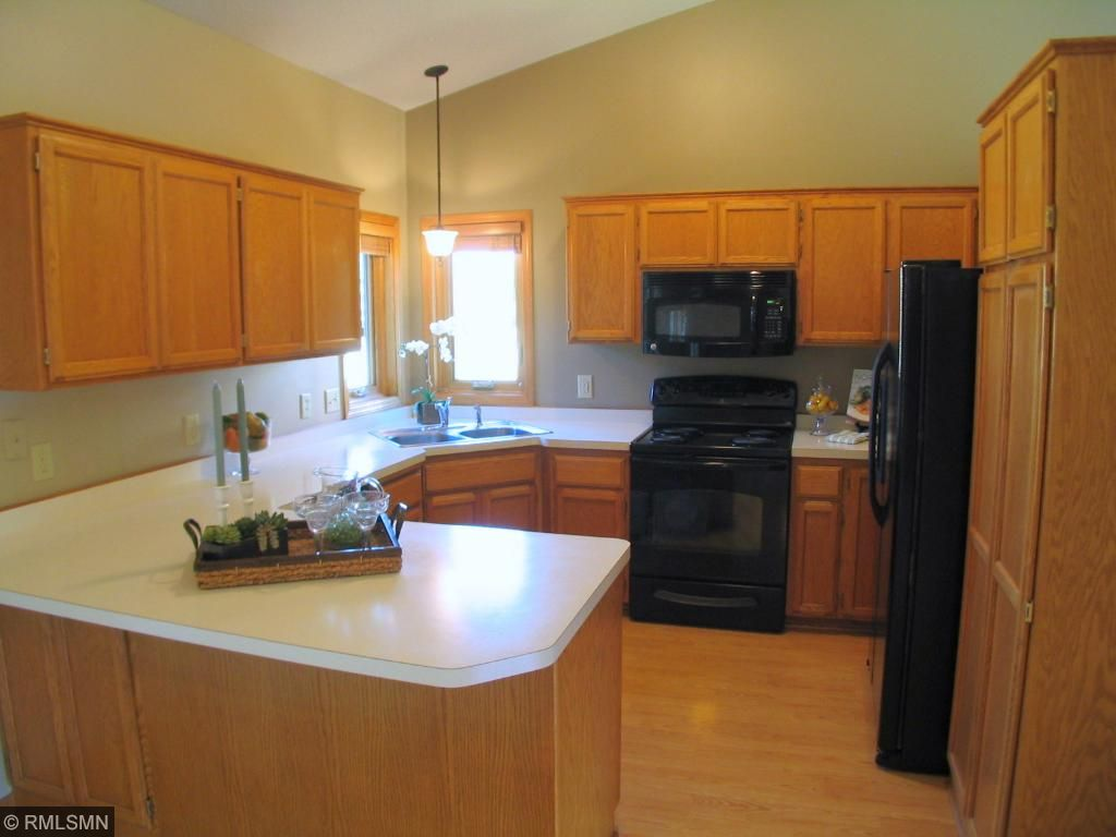 Bright and sunny kitchen with corner sink and designer appliances.