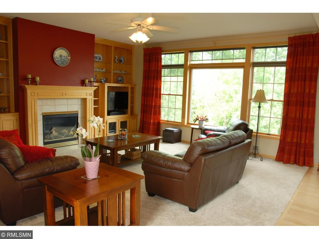 Living room has new carpeting, gas fireplace and large window overlooking trees.