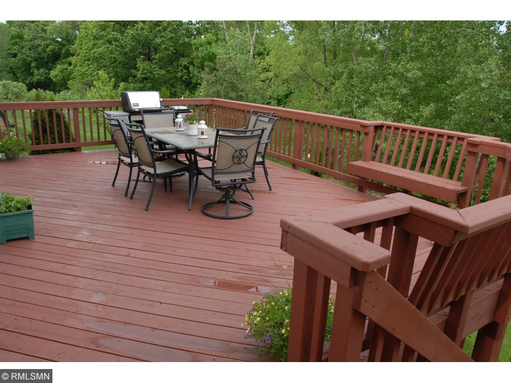Large deck with stairs leading down to fire pit.